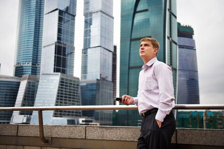 Thinking man with phone against backdrop of city  photo