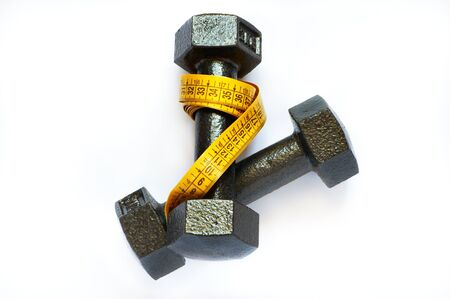 Dumbbells with measuring tape on white background photo