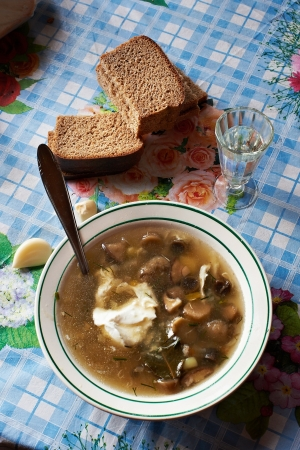 Mushroom soup and a glass of vodka at dinner table