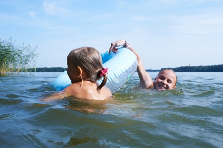 Two girls are swimming in a lake with inflatable toy