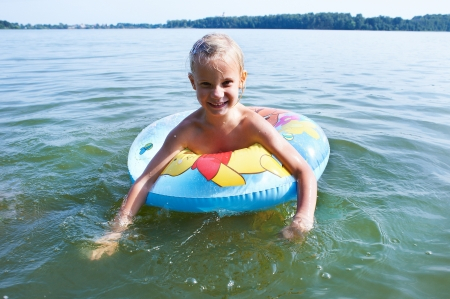 Girl swimming in a lake with inflatable toy photo