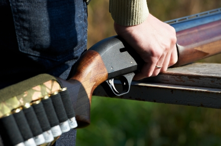 Shotgun with cartridges in hand hunter photo