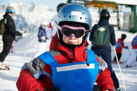 Little girl in blue helmet and red jacket on ski resort photo