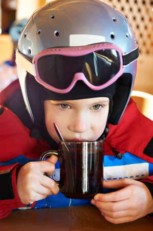 Child skier drinking tea in the competition photo