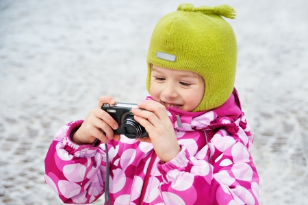 Funny little girl with compact camera