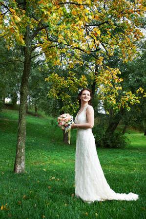 Happy bride in autumn park on wedding walk photo