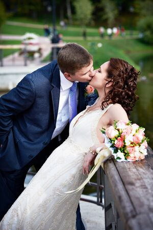 Romantic kiss bride and groom on wedding walk Stock Photo - 13758966