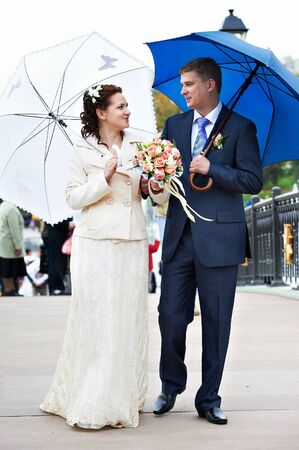 Happy Bride and groom at wedding walk with umbrella photo