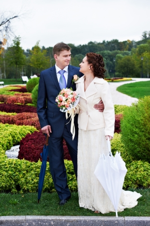 Happy bride and groom at wedding walk in park surrounded by flowers photo