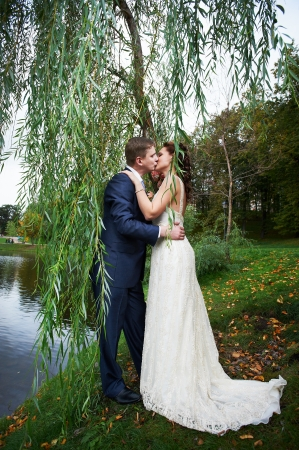 Romantic kiss bride and groom on wedding walk photo
