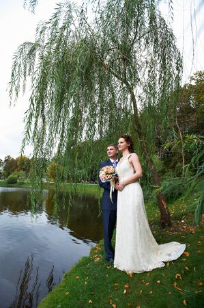 Happy bride and groom near lake and willow tree on wedding walk photo