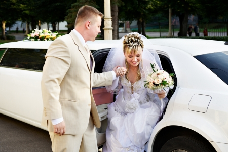 Happy bride and groom out of wedding limousine photo
