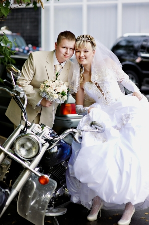 Happy bride and groom about stylish motorcycle photo