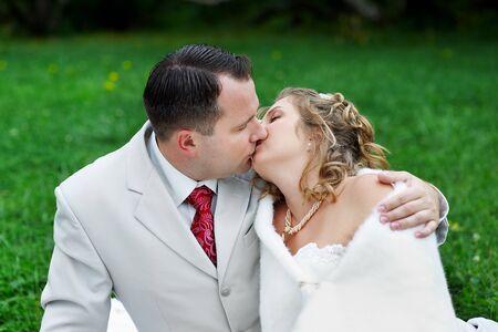 Romantic kiss bride and groom on wedding walk photo