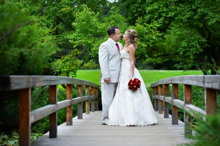 Happy bride and groom on a wooden bridge in the park at the wedding walk photo