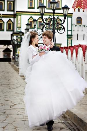 Groom carries his bride on his hands on bridge photo