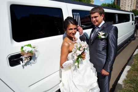 Happy Braut und Bräutigam in der Nähe Hochzeit Limousine