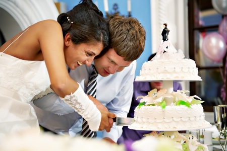 Happy bride and groom cut the wedding cake  Stock Photo