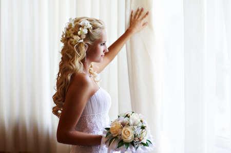 head dress: Happy bride in wedding dress with flowers near sunny window