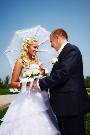 Happy bride and groom at wedding walk in park on background blue sky photo