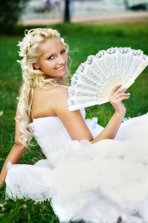 Happy bride with fan on grass at wedding walk photo