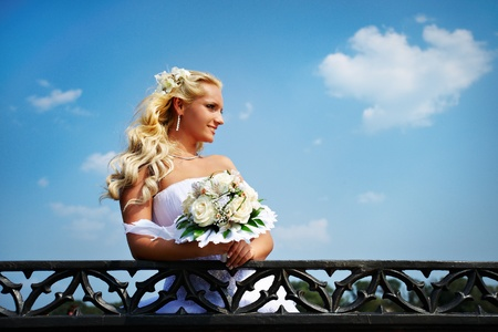 Beautiful bride with bouquet of flower at wedding walk in the park photo