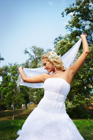 Beautiful bride with white cloth at wedding walk photo