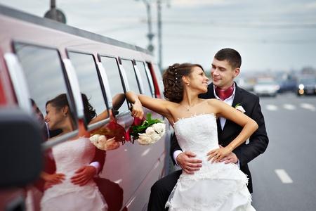 Happy bride and groom near wedding limo on walk