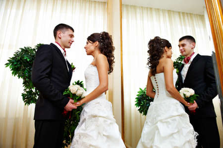 Romantic bride and groom near mirror in wedding palace photo