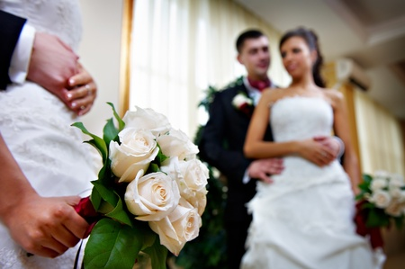 Bridal bouquet of flowers in her hand the bride and bridegroom in the mirror photo