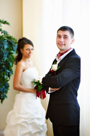 Happy bride and groom near bright window in wedding palace  photo