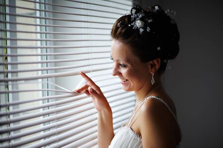 Happy bride at the window with the blinds photo