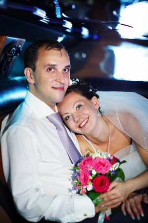 The bride and groom in a luxury wedding limousine photo