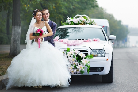 Happy bride and groom near wedding limo photo