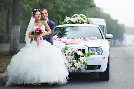 Szczęśliwa panna mÅ'oda i pan mÅ'ody w pobliżu limuzyny Å›lubnej Zdjęcie Seryjne