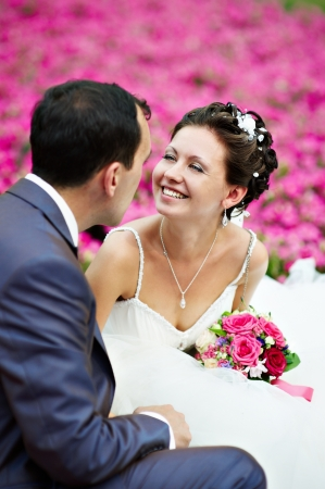 Happy couples on wedding walk on background of pink flowers Stock Photo