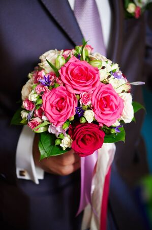 Flowers roses in hand of groom in wedding day photo