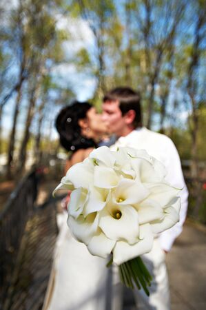 Kiss bride and groom with white bouquet photo