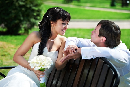 Bride and groom on the bench in park photo