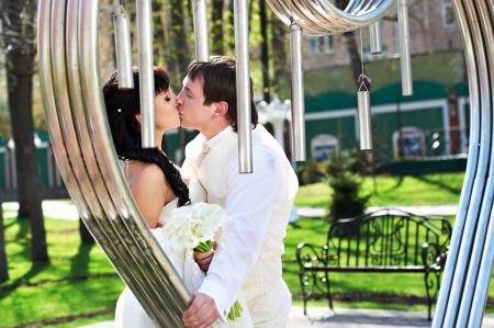 Romantic kiss bride and groom about art ironwork on wedding walk photo