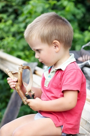 Little boy with slingshot in his hand photo
