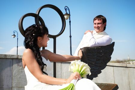 Bride and groom on bronze bench in wedding day photo