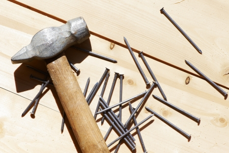 processing speed: Hammer and nails on wooden board Stock Photo