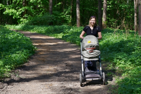 Woman with baby chair for a walk in park photo