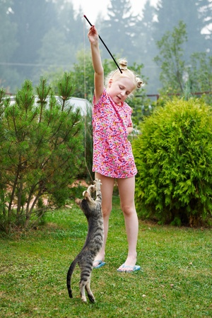 Girl playing with kitten in garden photo