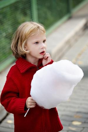 algodon de azucar: Niña en un suéter rojo que sostiene un caramelo de algodón Foto de archivo