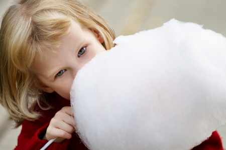 Little girl in a red sweater eating cotton candy