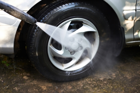 water jet: Washing car wheels with pressured water Stock Photo