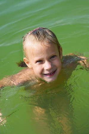 Little girl swimming in lake outdoors photo