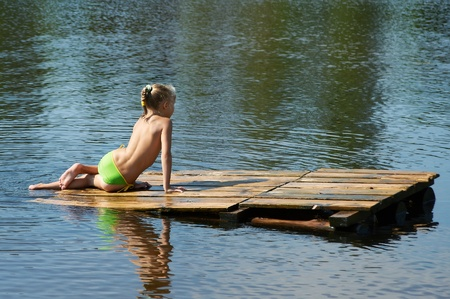 Little girl sits on a wooden raft